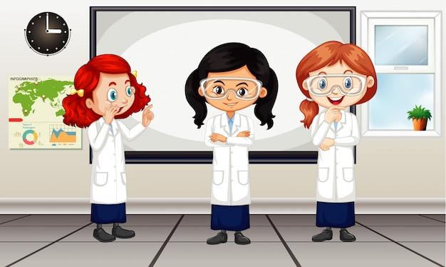 Klassenzimmerszene mit drei mädchen im laborkleid Kostenlosen Vektoren