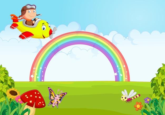 Kleiner junge, der eine fläche mit regenbogen betreibt Premium Vektoren