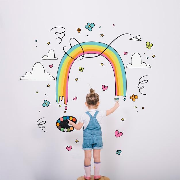 Künstlerisches kleines mädchen, das einen wunderbaren regenbogen malt Kostenlosen Vektoren