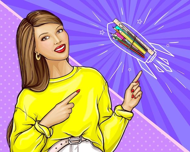 Lächelnde frau im gelben sweatshirt, das auf briefpapier, pop-art-illustration zeigt. werbebanner für grafikstudio-, bildungs- oder kunstkurse. zurück in die schule oder willkommen im schulkonzept mit dem lehrer Kostenlosen Vektoren