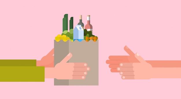 Lebensmittelgeschäft-zustelldienst mit der hand, die voll papiertüte lebensmittel gibt Premium Vektoren