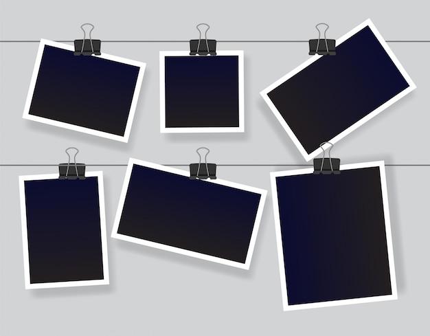 Leerer sofortbildrahmen, der an einem clip hängt. schwarze leere vintage fotorahmenvorlagen. illustration lokalisiert auf grauem hintergrund. Premium Vektoren