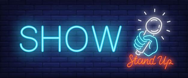 Leuchtreklame anzeigen. glowing stand up text und hand mit mikrofon Kostenlosen Vektoren