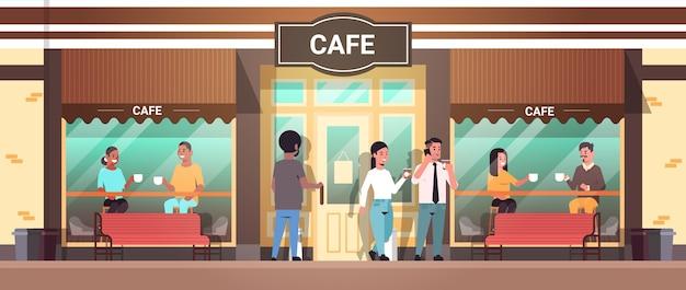 Leute, die an tischen sitzen männer frauen, die teemischungsrennenbesucher trinken, die kaffeepause modernes straßencafé außen haben Premium Vektoren