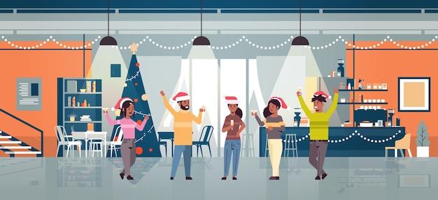Leute, die hände heben, die kaffeemännerfrauen in den weihnachtsmützen trinken, die spaß weihnachten neujahr winterferien feier konzept modernes café haben Premium Vektoren