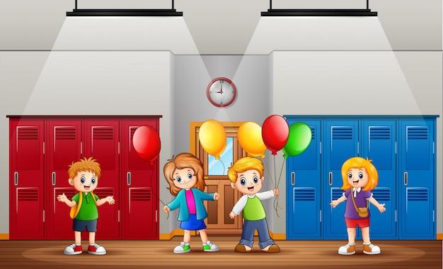 Lustige kinder, halten ballone vor der klasse Premium Vektoren