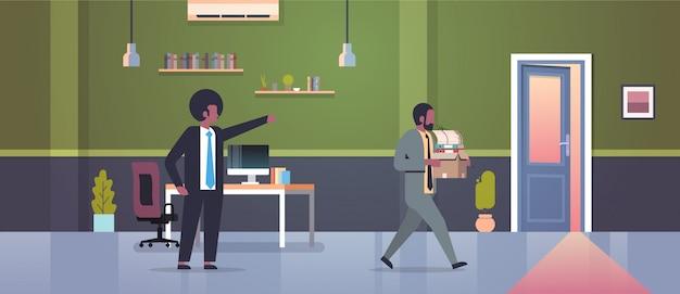 Männlicher chef entlässt das zeigen des fingers auf tür abgefeuerten mannangestellten mit papierdokumentenkastenentlassungsarbeitslosigkeit arbeitslosem konzept flachem modernem büroinnenraum Premium Vektoren