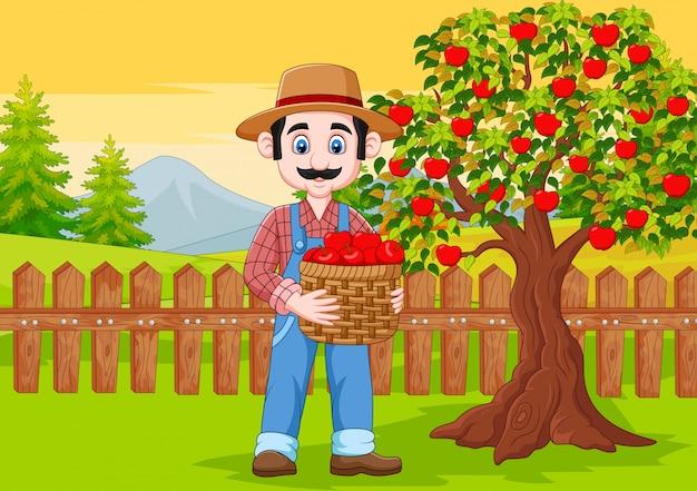 Männlicher landwirt der karikatur, der apfelkorb am bauernhof hält Premium Vektoren