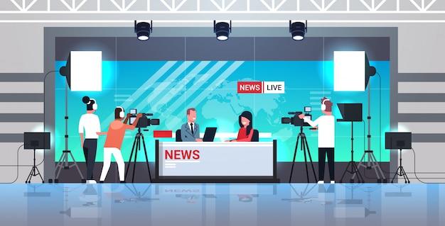 Männlicher moderator interviewt frau im fernsehstudio tv live-nachrichtensendung videokamera shooting crew broadcasting konzept flach in voller länge horizontal Premium Vektoren