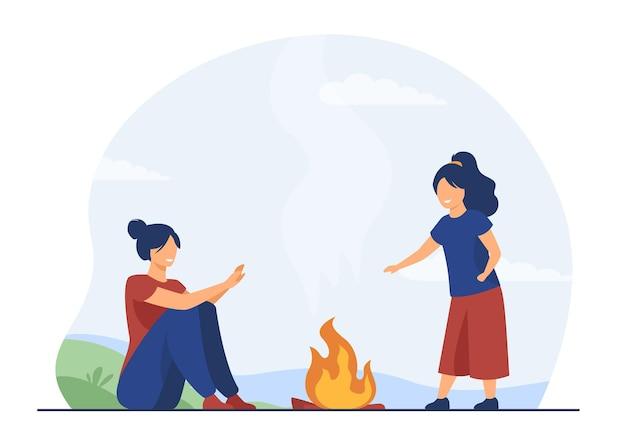 Mama und kind genießen camping im freien. glückliche frau und mädchen, die hände am feuer wärmen. karikaturillustration Kostenlosen Vektoren