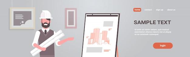 Mann architekt im helm hält blaupausen im rolleningenieur, der neues zeichnungsgebäude auf staffelei zeigt Premium Vektoren