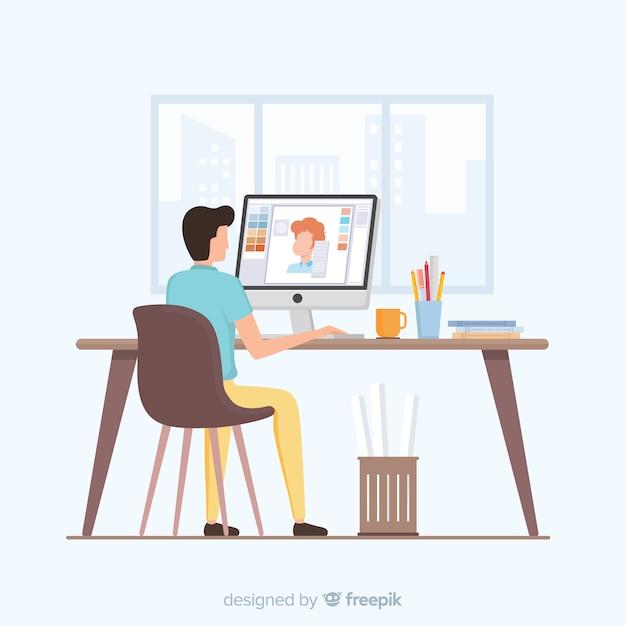 Mann, der am grafikdesignerarbeitsplatz sitzt Kostenlosen Vektoren