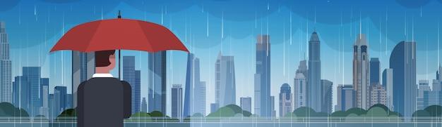 Mann, der regenschirm-blick auf sturm im stadt-enormen regen-hintergrund-hurrikan-tornado im stadtnaturkatastrophen-konzept hält Premium Vektoren