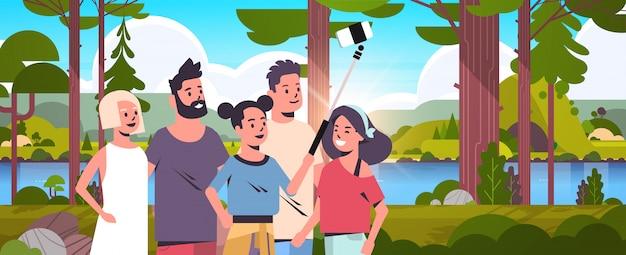 Menschengruppe im wald unter verwendung des selfie-sticks, der foto auf smartphone-kamera-wanderkonzeptfreunden nimmt, die zusammen landschaftshintergrundporträt horizontal stehen Premium Vektoren