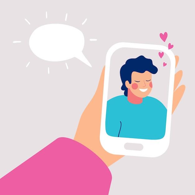 Menschliche hand hält mobilen smartphone mit lächelndem jungem mann auf anzeige. Premium Vektoren