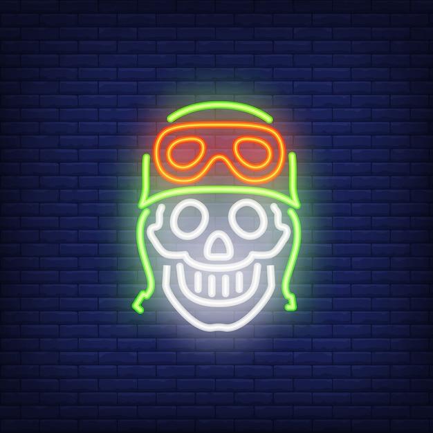 Menschlicher schädel im helm auf ziegelsteinhintergrund. neon-artillustration. motorradclub, motocross Kostenlosen Vektoren