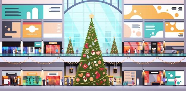 Moderne einkaufszentrummitte verziert für weihnachts- und neujahrsfeiertagskonzept große horizontale innenebene des einzelhandelsgeschäfts vieler leute Premium Vektoren