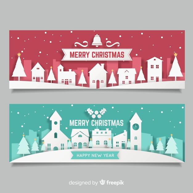 Moderne weihnachtsstadtfahnen in der papierart Kostenlosen Vektoren
