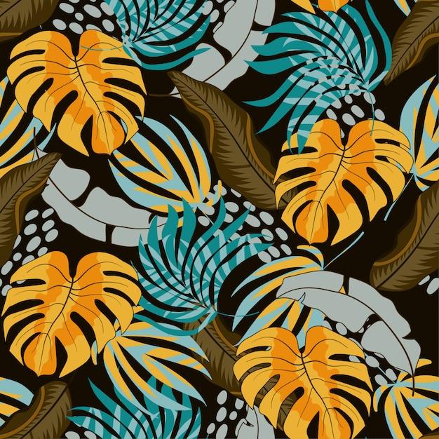 Nahtloses tropisches muster des sommers mit schönen gelben und blauen blättern und anlagen Premium Vektoren