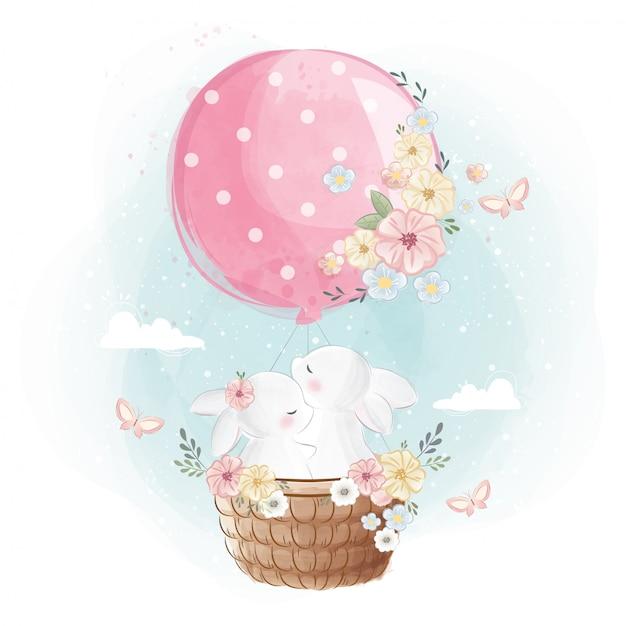 Netter hase, der mit einem ballon fliegt Premium Vektoren