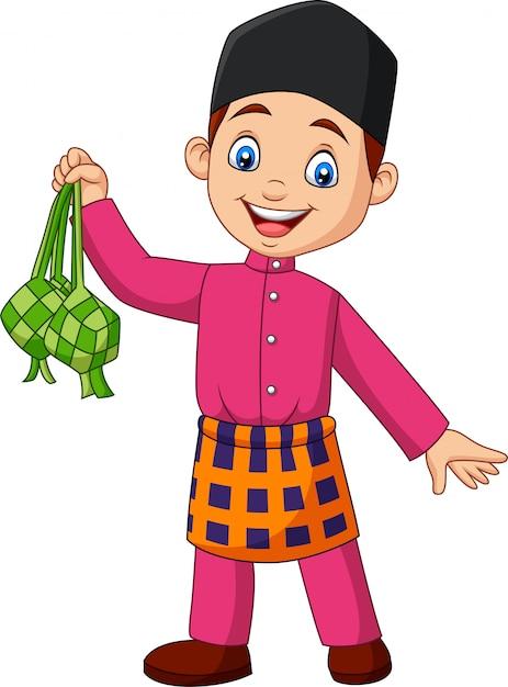 Netter moslemischer junge, der ein ketupat hält Premium Vektoren