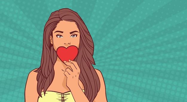 Nettes mädchen-schließender mund mit rotem herz-liebes-symbol über komischem pop-art valentines day concept Premium Vektoren