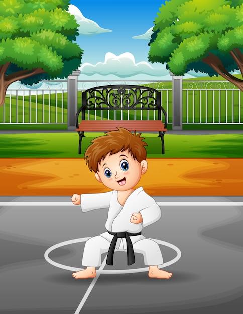 Nettes übendes karate des kleinen jungen im freien Premium Vektoren