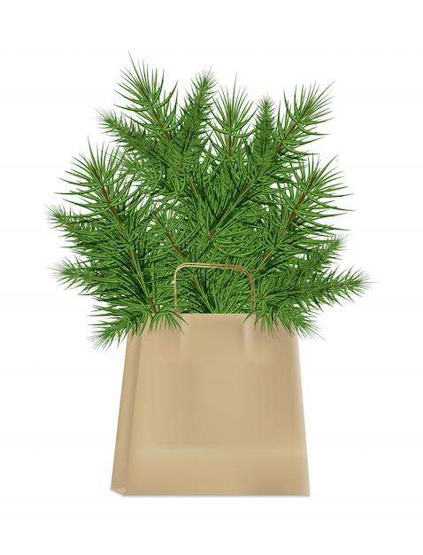 Niederlassungen des weihnachtsbaums im kraftpapierpaket lokalisiert auf einem weißen hintergrund Premium Vektoren