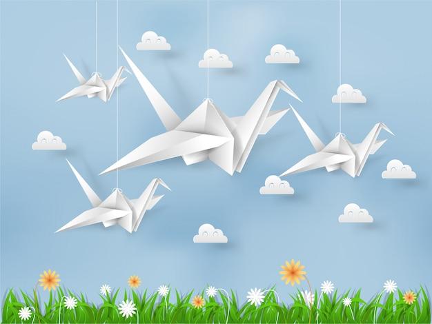 Origami vögel fliegen auf blauem himmel über feld von gräsern und blumen Premium Vektoren