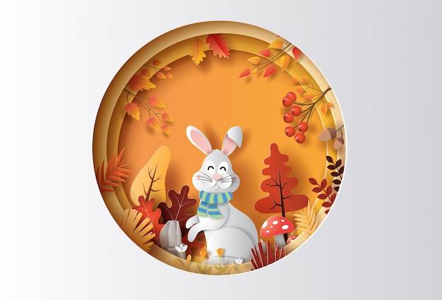 Papierkunstart des herbsthintergrundes mit kaninchen in einem wald, viele schöne blumen und blätter. Premium Vektoren