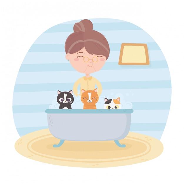 Pflege der alten frau, die katzen in der badewannenillustration badet Premium Vektoren