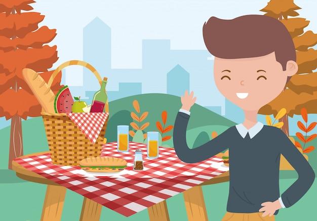Picknickkorblebensmitteltabellentischdecken-naturstadtbild des jungen mannes Premium Vektoren