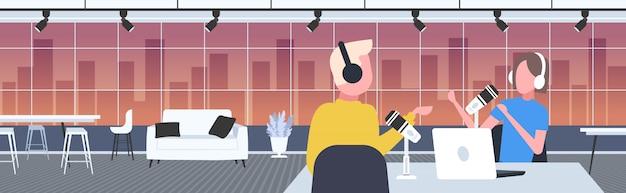 Podcaster sprechen mit mikrofonen aufzeichnung podcast im studio podcasting online-radio konzept mann in kopfhörern interview frau rundfunk porträt horizontal Premium Vektoren