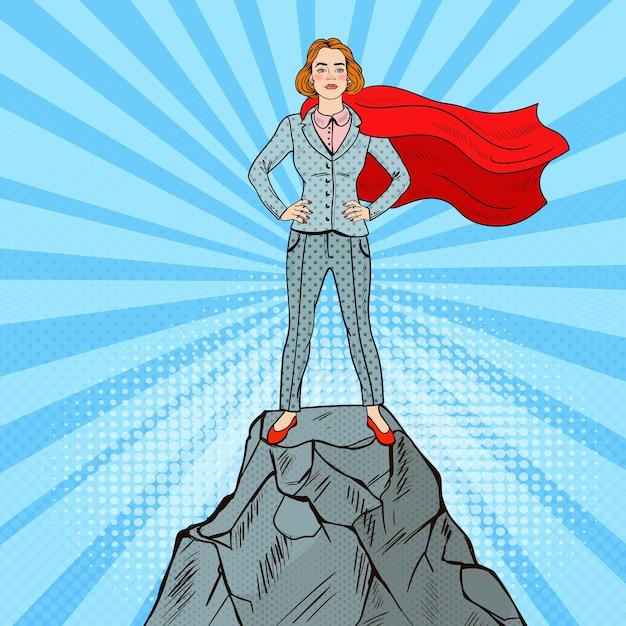 Pop art selbstbewusster superheld der geschäftsfrau im anzug mit dem roten kap, das auf dem berggipfel steht. Premium Vektoren