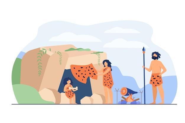 Prähistorisches familienpaar und kind, das leopardenfelle trägt und essen am höhleneingang kocht. vektorillustration für steinzeitalter der alten leute, höhlenmensch-abendessenkonzept Kostenlosen Vektoren