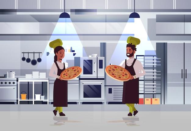 Professionelles kochpaar, das tabletts mit frischer pizza afroamerikaner-mannfrau in uniform hält, die zusammen kochendes lebensmittelkonzept modernes restaurantkücheninnenraum stehen Premium Vektoren