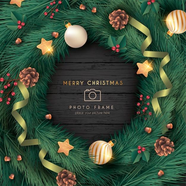 Realistischer weihnachtsfotorahmen mit verzierungen und blättern Kostenlosen Vektoren