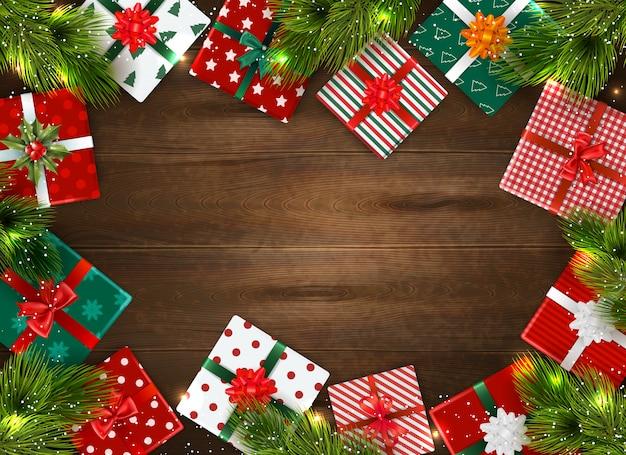 Realistischer weihnachtshintergrund mit bunten geschenkboxen und tannenzweigen auf holztisch Kostenlosen Vektoren