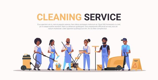 Reinigungsteam in uniform zusammen reinigungsservice konzept männliche hausmeisterinnen mit professioneller ausrüstung in voller länge horizontalen kopierraum Premium Vektoren
