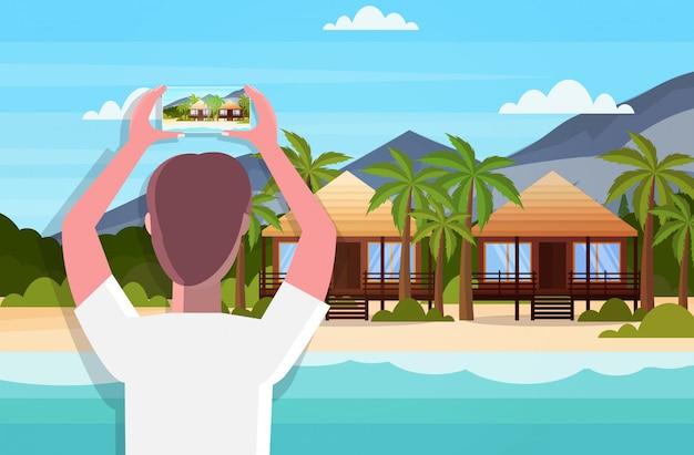 Reiseblogger unter verwendung der smartphone-kamera, die foto oder video des tropischen strandes mit bungalows aufnimmt, die live-streaming-sommerferienkonzept-seestückhintergrund horizontales rückansichtporträt bloggen Premium Vektoren