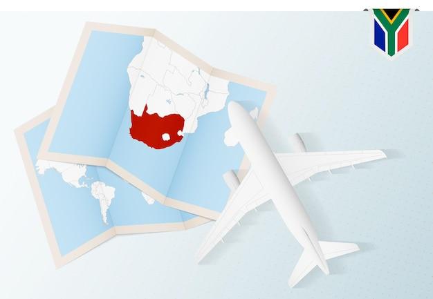 Reisen sie nach südafrika, draufsichtflugzeug mit karte und flagge von südafrika. Premium Vektoren