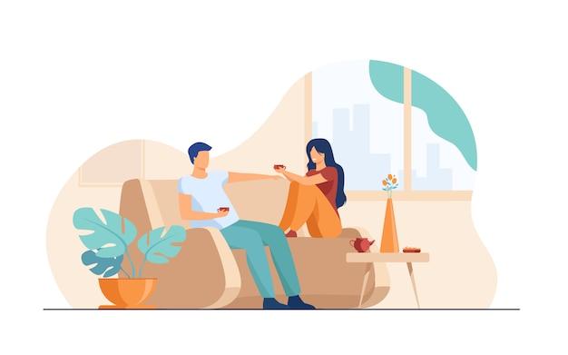 Romantisches paar, das am sofa sitzt, redet und kaffee trinkt Kostenlosen Vektoren