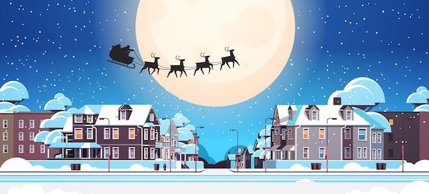 Santa fliegt im schlitten mit rentieren im nachthimmel über dorfhäusern frohes neues jahr frohe weihnachten banner winterferien konzept horizontale vektor-illustration Premium Vektoren