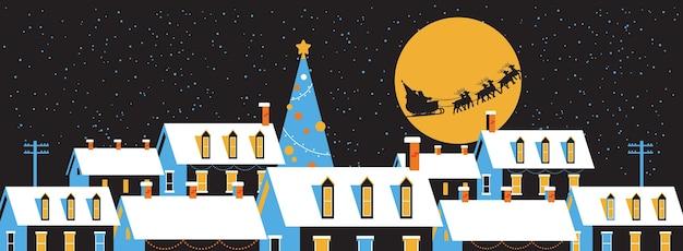 Santa fliegt im schlitten mit rentieren im nachthimmel über schneebedeckten dorfhäusern frohe weihnachten winterferien konzept grußkarte flach horizontal Premium Vektoren