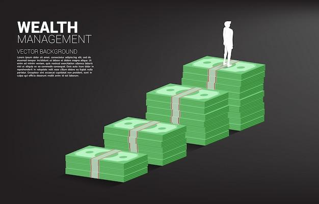 Schattenbild des geschäftsmannes stehend auf wachstumsdiagramm mit stapel der banknote Premium Vektoren