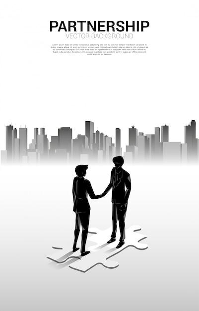 Schattenbild des geschäftsmannhändedrucks auf stichsäge mit stadthintergrund. konzept der teamarbeit partnerschaft und zusammenarbeit. Premium Vektoren