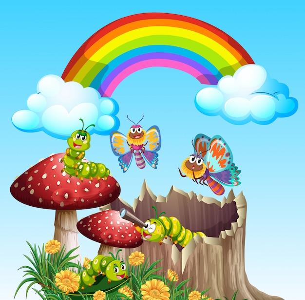 Schmetterlinge und würmer, die tagsüber in der gartenszene mit regenbogen leben Premium Vektoren