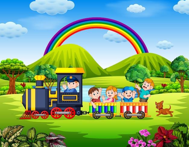 Schöne aussicht mit den kindern im zug weht unter dem regenbogen Premium Vektoren