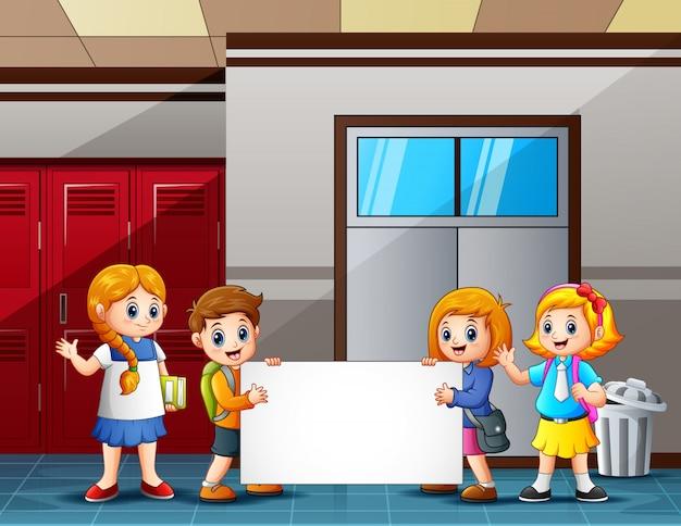 Schulkinder, die ein leeres zeichen vor dem klassenzimmer halten Premium Vektoren