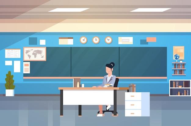 Schulklassenzimmer-innenlehrerin, die am schreibtisch über kreide-brett im klassenzimmer sitzt Premium Vektoren